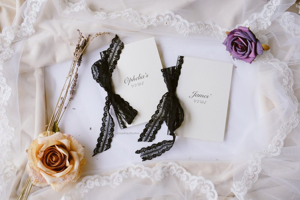 Textured felt paper vow booklets bound with black lace ribbons.
