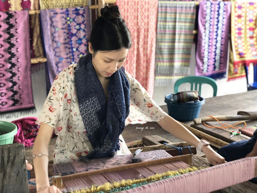 Me trying my hand at the weaving loom.